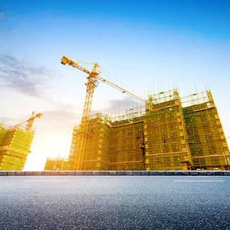concrete commercial block: Construction site, workers and cranes. Stock Photo