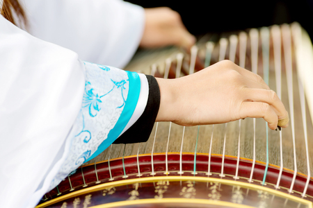 entertainment equipment: A girl is playing Guzheng.The guzheng or gu zheng, also simply called zheng, is a Chinese plucked zither. It has 18 or more strings and movable bridges.