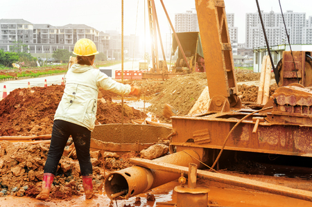 dredging: Woman worker is dredging at construction site