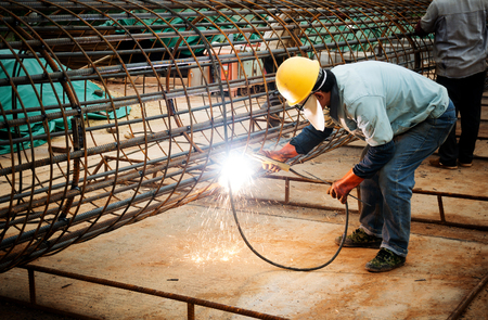 laborers: welder worker welding metal by electrode with bright electric arc and sparks during manufacture of metal equipment Stock Photo