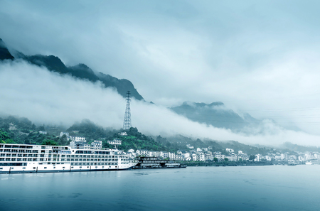 yangtze river: Travel on the Yangtze River with a view of the mountains and the town
