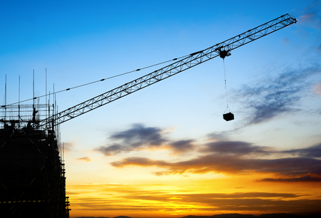 cranes: Construction sites, cranes and workers sunset silhouette. Stock Photo