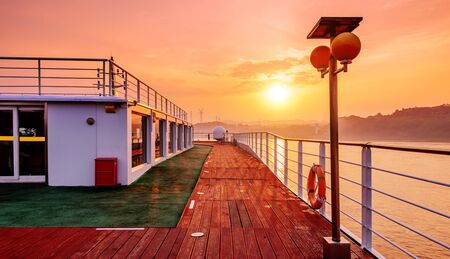 Cruise ship deck, morning sun shines on the floor, a piece of red. Stock Photo