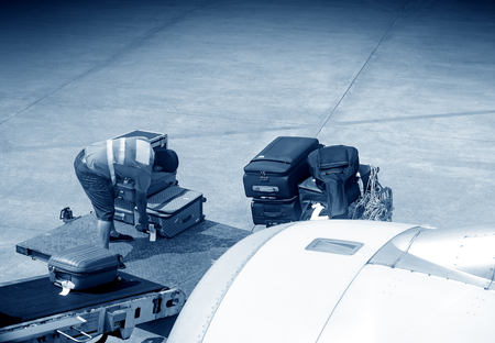 onto: A man is loading luggage onto airplane