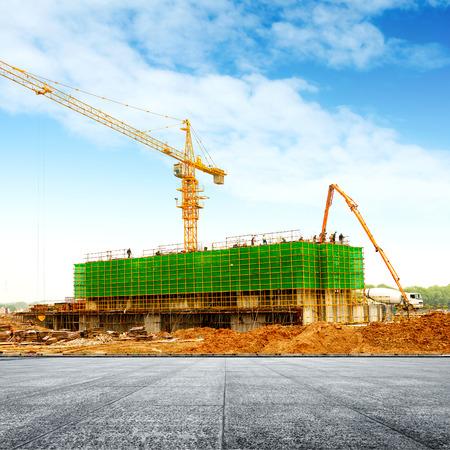 anuncio publicitario: Obra de construcción, los trabajadores y las grúas.