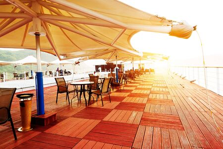 ship deck: Cruise ship deck, morning sun shines on the floor, a piece of red. Stock Photo