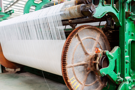 A row of textile looms weaving cotton yarn in a textile mill. Imagens