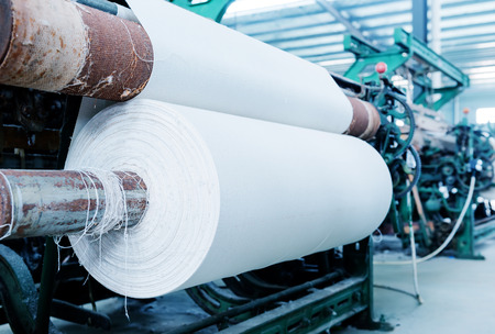 polyester: A row of textile looms weaving cotton yarn in a textile mill. Stock Photo