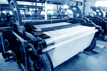 A row of textile looms weaving cotton yarn in a textile mill. Banco de Imagens