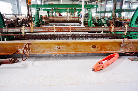 A row of textile looms weaving cotton yarn in a textile mill. Stock Photo