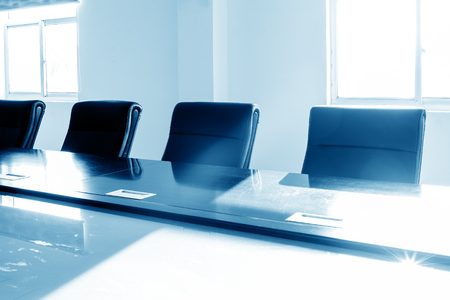 furnishings: The sun shines on the tables and chairs in the conference room, with blue tones.