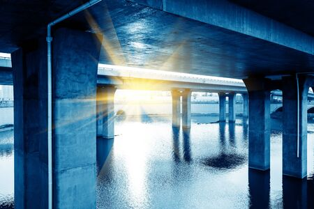 water transportation: Bridge at the bottom of piers, modern building blue tones. Stock Photo