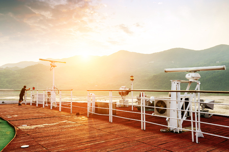 On the deck of a cruise, the man looks at the sunrise in the morning.