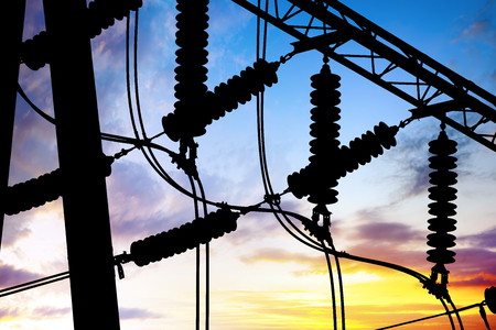 Substation lines and equipment, silhouette at dusk.