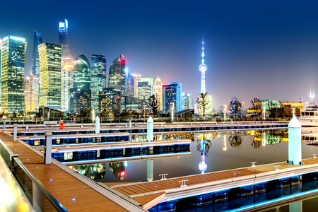 Cityscape of Shanghai Downtown at night reflected in the river, China