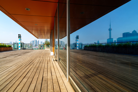 The wooden pedestrian path along the Huangpu River reflects the tall buildings in Pudong, Shanghai, China.