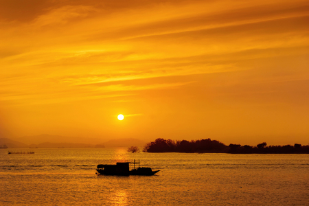Silhouette of fishing boat at sea during sunset
