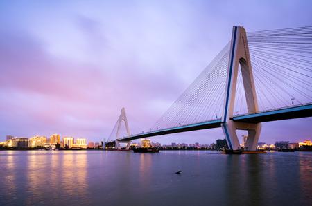 El horizonte de la ciudad y el puente del mar en la noche, Haikou, Hainan, China
