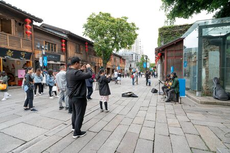 Sanfang Qixiang (Three Lanes and Seven Alleys), Fuzhou, China - 07 May 2019: A famous tourist destination, tourists watched by street singers. 新闻类图片
