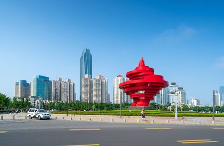 QINGDAO, CHINA - June 14, 2019: May Wind Sculpture at May Fourth Square in central business district of Qingdao with Chinese skyscrapers Редакционное