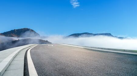 In the early morning, the road crosses the foggy mountains, Inner Mongolia, China. Фото со стока