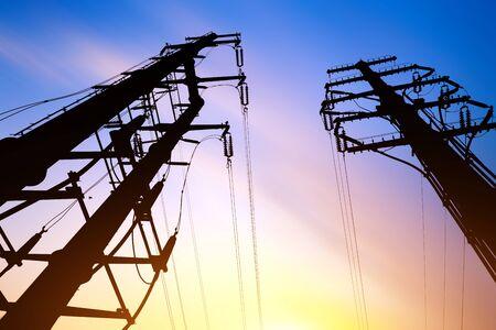 Postes de electricidad de alto voltaje y cielo al anochecer