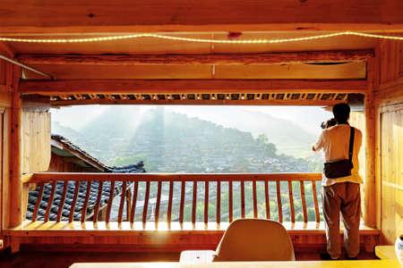 A man is photographing the ancient village of Miao Village in Xijiang, Guizhou, China. Foto de archivo