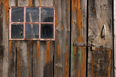 Old weathered and worn wooden planks with door and pink framed window Stock Photo
