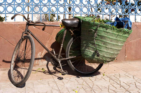 tatty: Old bicycle leaning against wall with panniers on the back