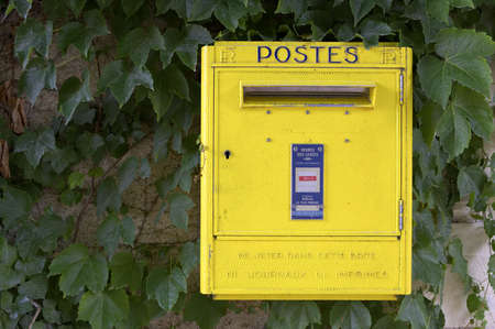 Yellow French post box on wall, chateau de chenonceau Stock Photo