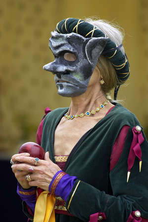 mediaeval: Woman wearing a mediaeval mask while holding a red apple Stock Photo