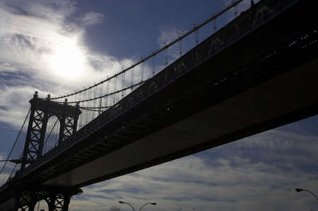 Brooklyn Bridge spanning the east river, viewed from underneath and into the sun, Manhattan, New York, America, usa photo