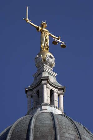 equidad: Estatua de la justicia, una mujer que ocupe un cargo espada en la mano derecha de pie para el poder de castigar y un equilibrio en la mano izquierda por la equidad de pie en el tejado de la antigua bailey, oficialmente conocido como el tribunal penal central london england uk europa tomado i