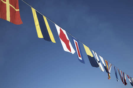 maritime: nautical flags strung along the line of a cruise ship Stock Photo