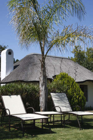 loungers: empty sun loungers outside a small thatched house knysna western cape province south africa Stock Photo