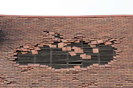 damaged roof: roof of an old derelict house with a large hole exposing the timber rafters which would support the tiles bedworth coventry uk Stock Photo