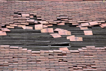 roof of an old derelict house with a large hole exposing the timber rafters which would support the tiles bedworth coventry uk Stock Photo