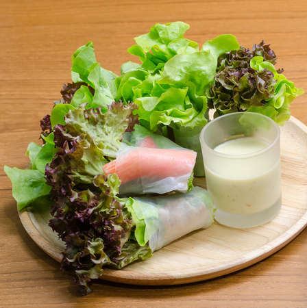 salad dressing: Salad roll vegetables and crab stick with salad dressing in wooden plate