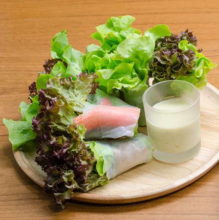 ensalada: Verduras rollo ensalada y palo de cangrejo con aderezo de ensalada en un plato de madera Foto de archivo