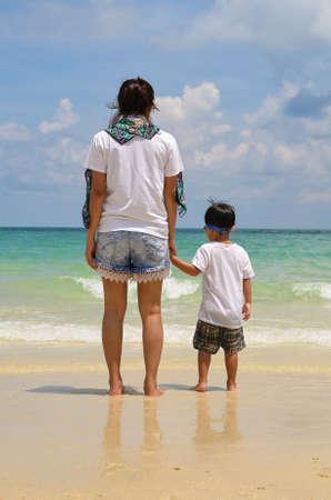 Mujer y niño tomados de la mano y de pie en la playa