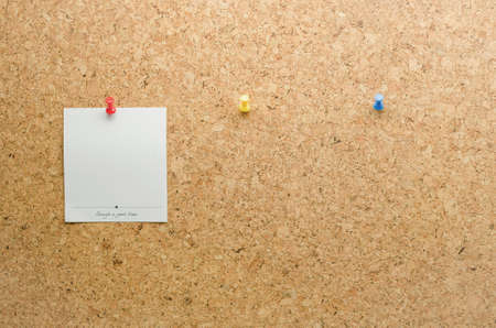 tack board: Paper card posted on a cork board with tack pin and waiting paper cards for the other tack pins