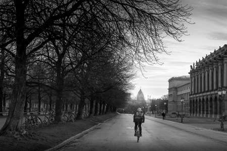 packsack: student cycling on the road in evening on winter day, Germany, Europe.