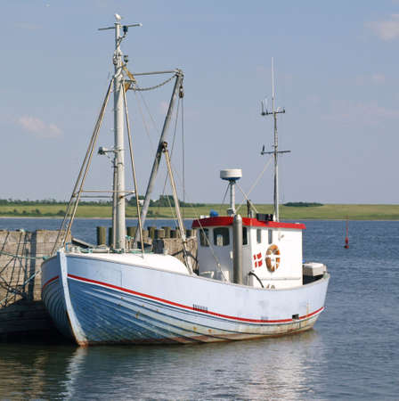fishingboat: Lightblue fishingboat along a wooden pier, a seagull is sitting atop the mast.      Stock Photo