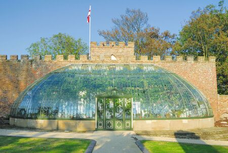 full shot: Full shot of an ornate Victorian greenhouse that has been built up against a brick wall.
