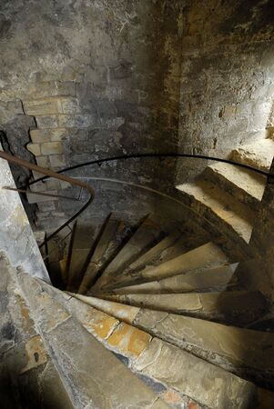 hand rails: Spiral staircase in a castle with hand rails and a small window.