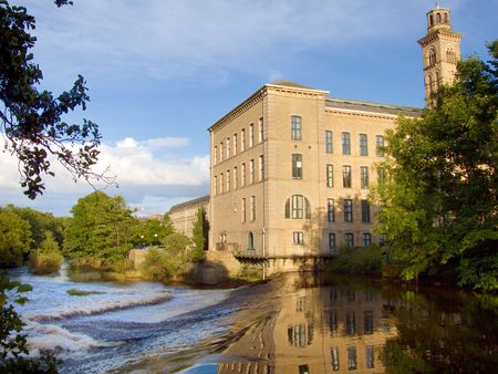 salts: Salts mill viewed from across the River Aire in the early evening. Stock Photo
