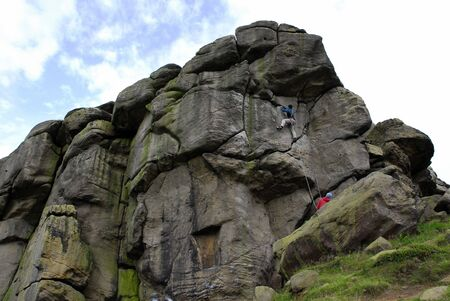 overhang: Climber on the face of Almscliff Cragg approaching the overhang.