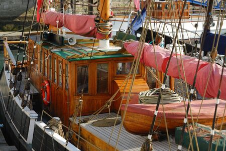 wheelhouse: View of an old wooden sailing boat showing deck and wheelhouse.