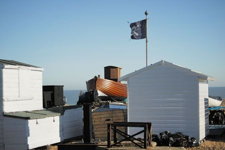 flagpoles: Beach hut flying a skull and cross bones with a wooden boat in the background