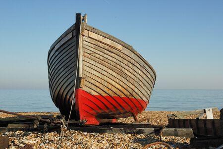 kiel: Boeg van een boot met een rode kiel die is getrokken up op het strand